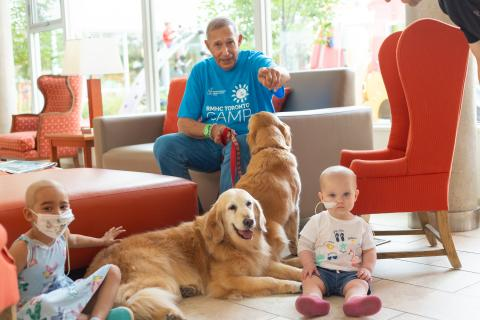 Photo of George Cohon with two girls and two therapy dogs